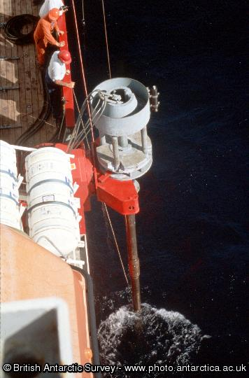 Long Piston Corer lowered into position but still clamped to ship (JCR) during sea trials. The Long Piston Corer has the ability to take virtually undisturbed cores of the sediment on the seabed. This is achieved by using a stationary piston which is held in contact with the sediment surface through a series of wires and pulley wheels which are attached to a base plate on the seabed. Using this method the corer is able to penetrate the sediment under its own weight independently of the ship's motion.