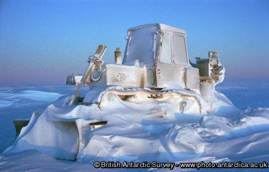 The reality of winter at Halley research station where temperatures may drop below -50 degrees Celsius.  An International Harvester Bulldozer is encased in a frost of spin-drift and drifted snow through the winter of 1995.  Once the bulldozer's engine preheaters are switched on, the vehicle could be running in an hour.