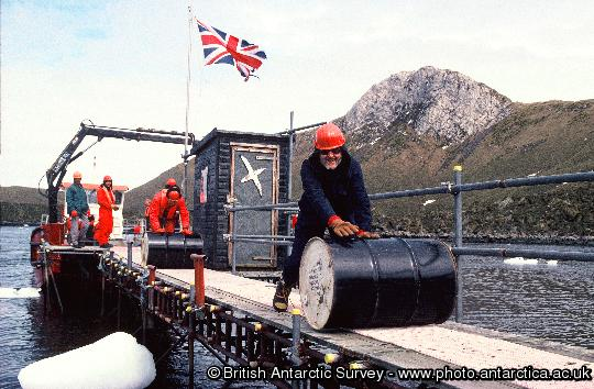 John Dudeney helps roll fuel drums to the base during the annual relief at Bird Island