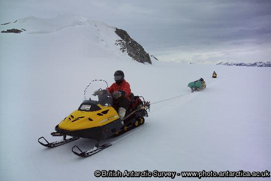 Two-man skidoo team roped together for safe field travel.