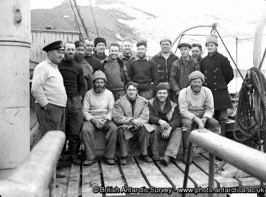 Operation Tabarin members on the deck of the Royal Navy ship H.M. S. Eagle at Deception Is.  Shows: (standing left to right) Berry, James, Matheson, Russell, Lamb, Farrington, Donnachie, Reece, Taylor, Davies, Smith, Back; (sitting left to right) Ashton, Blyth, Marshall, Flett.