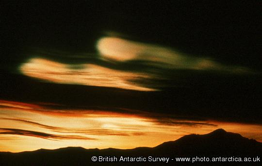 Nacreous (also known as mother of pearl or stratospheric) clouds.  These clouds form at around 20km altitude in the ozone layer and are instrumental in the process of ozone depletion.  Because of their altitude they remain illuminated by the sun, long after sunset on the ground.