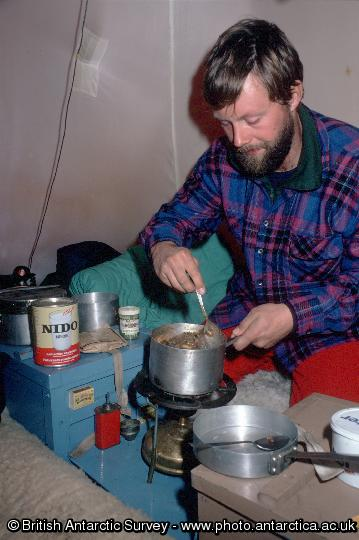 Preparing a meal inside a pyramid tent