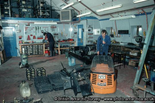 Mechanic working on a ski-doo in the garage at Rothera Research Station. Snow-mobiles are extensively used at the BAS stations and at remote field locations. These small vehicles are used for personal transport and for towing Nansen sledges. BAS operates Bombardier Ski-doos which are simple to ride with just a twist grip throttle and a brake. They have a fully automatic transmission and a track underneath with skis at the front to steer. Ski-doos can attain speeds of up to 50 mph on smooth snow.