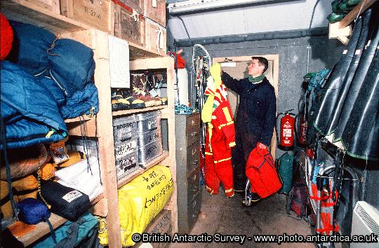 Bird Assistant Daf' Roberts hangs up small boat suits in the 'outdoor clothing and rescue store' at Bird Island