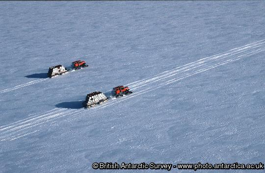 Aerial view of two sno-cats transporting empty drums from Halley Research Station to the ship for crushing and disposal outside Antarctica