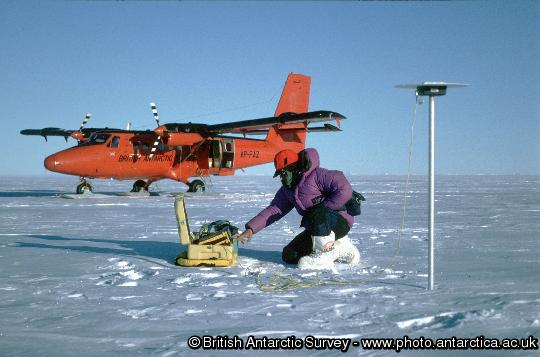 A glaciologist uses Twin Otter aircraft and GPS to survey the flow of the ice sheet.  The pole on which the antenna is mounted will be re-visited.  Measuring the speed of ice-flow allows glaciologists calculate whether the ice sheet is changing.  Here a glaciologist uses a Global Positioning System receiver to measure the position of an alumimium pole planted in the snow.  Remeasurement of its position after a year's movement will allow the ice-flow speed to be determined.  The measurement only takes one hour, so it can be efficiently supported by aircraft.