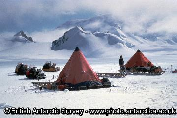 Field training camp on an ice field below Trident Peak, southern Adelaide Island. BAS staff must undergo training and familiaristaion with all equipment to be used in the field, both in Cambridge and on arrival in the Antarctic.  Ttwo field units (tent, sledge, skidoos) are shown.