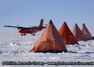 BAS Twin Otter aircraft and row of pyramid tents at an ice core drilling camp