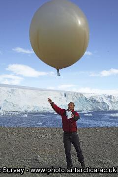 A scientist launches a meteorological balloon at Rothera Research Station.