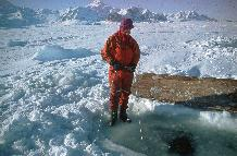 Linesman (Stuart Wallace) monitoring life line for divers working under one metre thick fast ice winter 1997.
