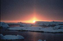 Sunset with Sun pillar across icebergs. The sun pillar is created by ice crystals in the air reflecting sunlight.