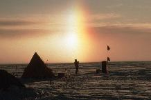 Sun dog formed in light falling snow  The light from the sun is refracted by the ice crystals to form parhelia, or sun-dogs.