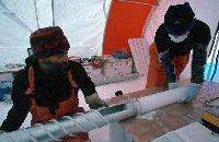 International European Project for Ice Coring in Antarctica (EPICA) project: Dronning Maud Land reconnaissance phase.  Scientists remove a core from the barrel of an ice core drill: analysis of the ice, which fell as snow more than 1000 years ago, will reveal changes in climate and the composition of the atmosphere.