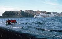 Tourists being taken ashore in an inflatable named Charles Darwin from tourist ship Hanseatic at Whalers bay, Deception Island , Cathedral Crags in background .