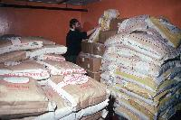The Rothera cook and sacks of flour in the food store at Rothera.